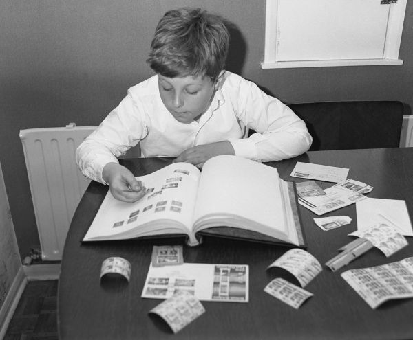 A little boy working on his stamp collection at a table. He has various stamps laid out, and is sticking them carefully into an album