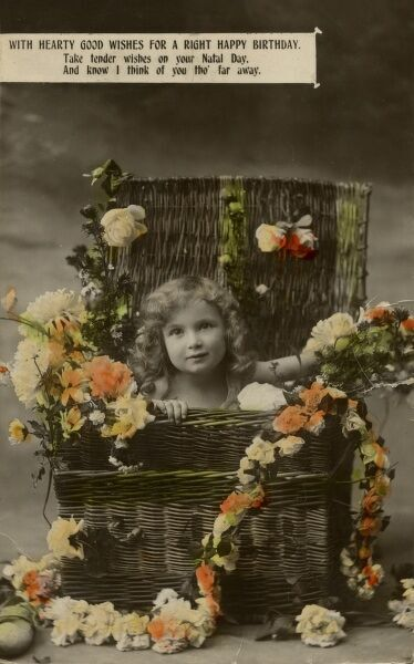 A little girl sitting inside a basket, surrounded by flowers, on a birthday postcard