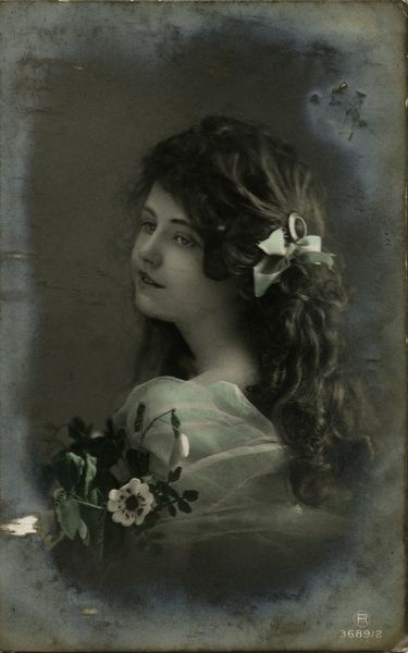 A pretty little girl with dark curly hair and a bunch of white flowers