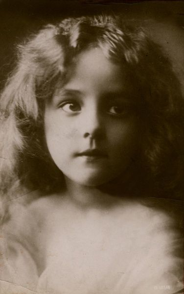 A pretty little girl with a dreamy look on her face.  1915