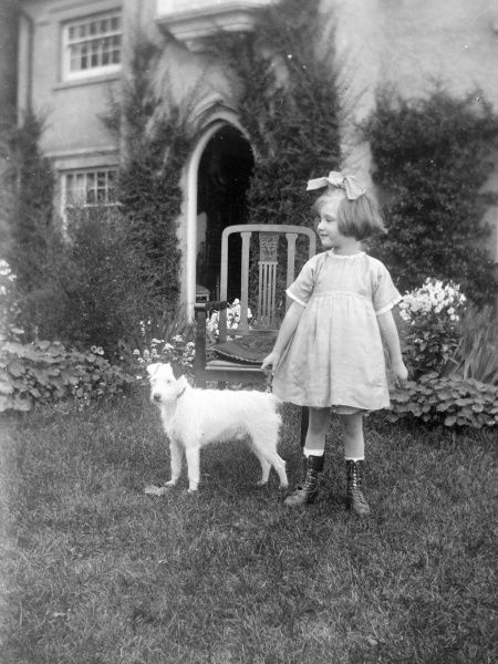A little Edwardian girl in a garden with a small wire-haired terrier dog