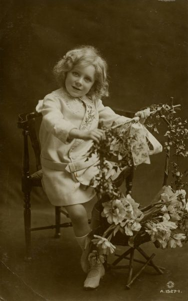 A little girl with a garland of flowers on a wooden frame. (1 of 2) Date: 1915