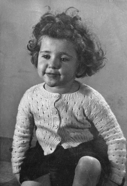 A little girl in a knitted cardigan, relaxed and smiling. She has short, curly hair