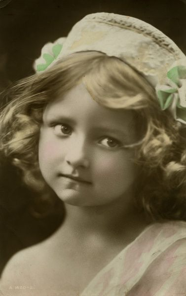 A cute little girl in a lacy white hat with green trimmings.  1915