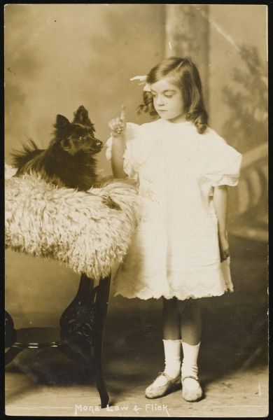 A smartly dressed little girl wearing a white dress, ribbon and ringlets, tells her dog to sit and stay for their portrait
