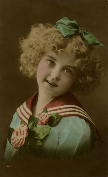 A pretty little girl in a red, white and blue sailor suit, with pink and white flowers. She has a green ribbon in her curly blond hair