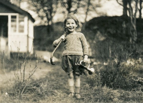 A little girl with a walking stick and a toy bugle, somewhere in Scotland
