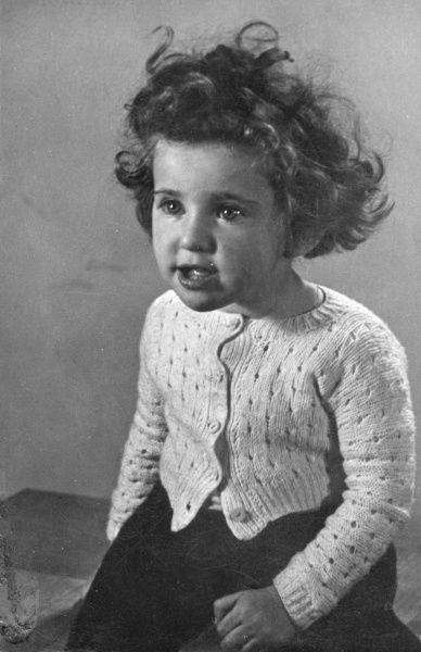 A little girl who appears to have been crying, but is now recovering as something has attracted her interest. She is sitting on a table top, wearing a knitted cardigan and a dark skirt