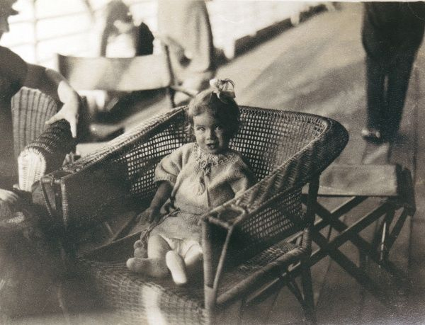 A little girl sitting in a wickerwork chair, looking directly up at the photographer, somewhere in the Middle East