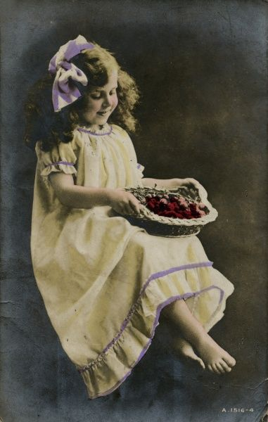 A little girl in a frilly yellow dress with a basket of fruit on her lap