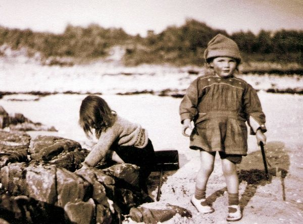 Two little girls on a beach, somewhere in Scotland. The girl on the left is investigating something in a rock pool