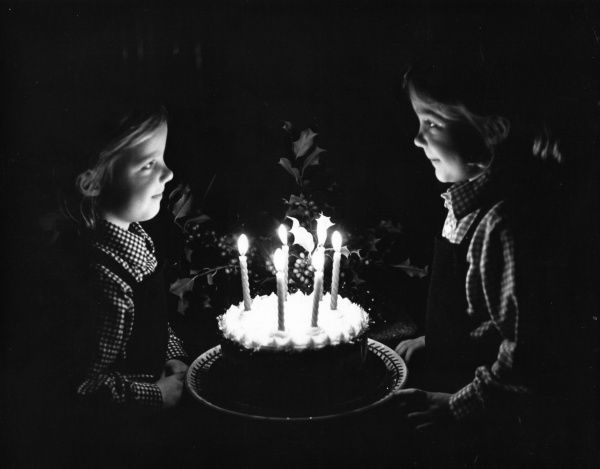 Two little girls smile at each other across a birthday cake with six lighted candles