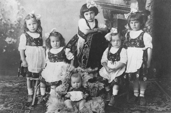 Five little girls and a baby wearing traditional East European folk costume, probably from Moravia or Slovakia