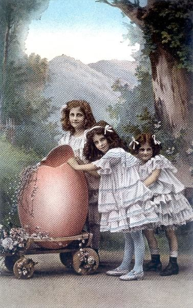 Three little girls with a large pink Easter egg, so big they have to wheel it on a trolley !