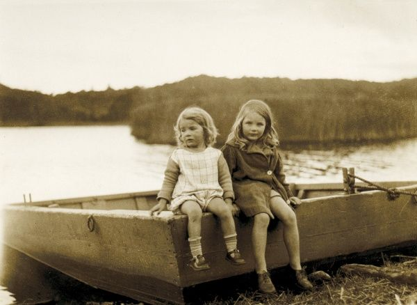 Two little girls sitting on the edge of a boat, at the water's edge, somewhere in Scotland