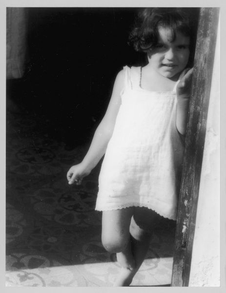 A little Italian girl in a white dress with lace trim, part of the Italian immigrant community living in the Saffron Hill area of London