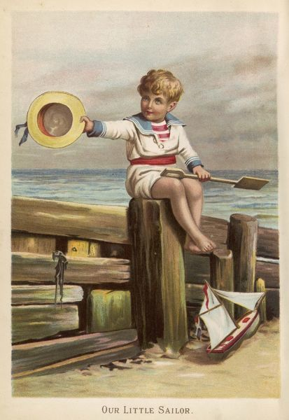 Blonde sailor boy in red & white striped shirt, white sailor blouse with blue collar & a red sash sits on a wave break with a toy boat & spade waving his straw sailor hat
