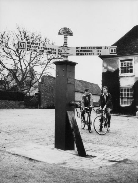 Two young men on a cycling tour, take time out to admire the old village pump in the centre of Littlebury, Essex, England. Date: 1940s