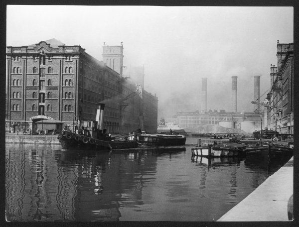 The Princes Half-tide Dock, Liverpool, Merseyside, England, showing a steam ship pulling an industrial barge