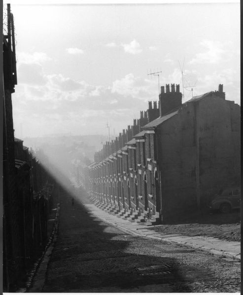 A street in Liverpool with a long row of terraced houses sloping down the hill