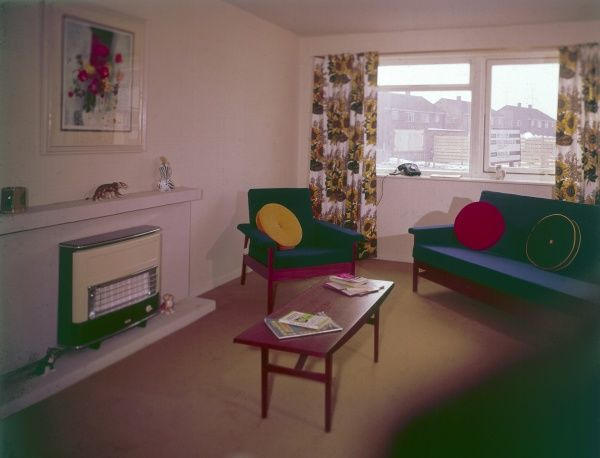 The living room of a council house, with gas fire, coffee table, simple sofas and armchairs with colourful scatter cushions. Date: 1964
