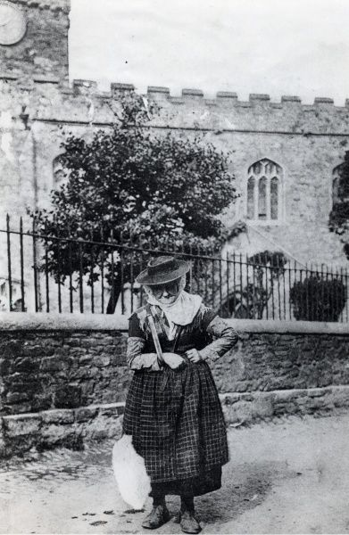 An elderly cockle woman from the coastal village of Llangwm rests outside St Mary's Church in Haverfordwest, Pembrokeshire, Dyfed, South Wales