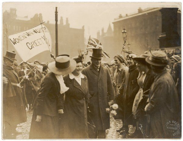 DAVID LLOYD GEORGE accompanied by Flora Drummond and Phyllis Ayrton, greets women munitions workers towards the end of World War One