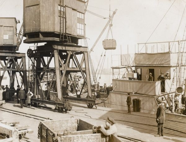Loading up a boat destined for France at a supply depot somewhere in the UK during the First World War. Date: 1914-1918