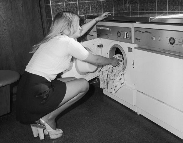 "A young housewife loading up her ""Miele"" washing machine (with matching dishwasher) in her mini skirt and platform shoes"
