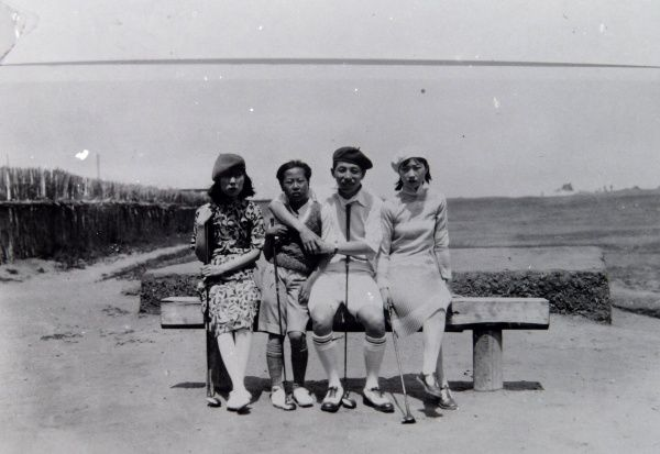 Four local people, two men and two women, sitting on a bench, somewhere in the Far East. They are wearing fashionable, western style clothing and are holding golf clubs. There is a golf course in the background