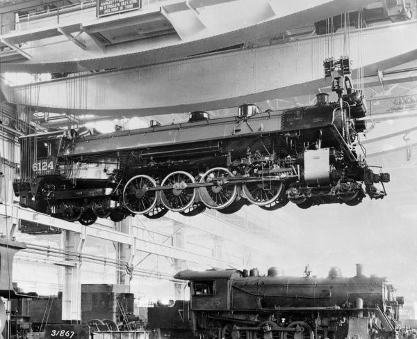 A brand new giant locomotive under construction, suspended from a steel girder. When finished, it will grace the Canadian Pacific Railway. Date: 1930s