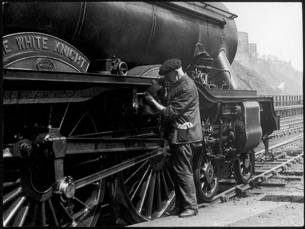 A maintenance man checking over 'The White Knight' steam locomotive at Waverley Station, Edinburgh, Midlothian, Scotland