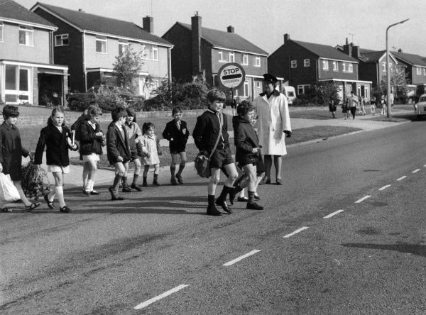 A lollipop lady stands in the middle of a very quiet residential road to assist a group of schoolchildren to cross it. Date: early 1970s