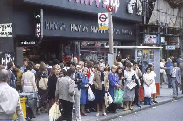 A miserable scene at a London bus stop, showing a crowd of people waiting for a bus during the Rush Hour. Date: 1979