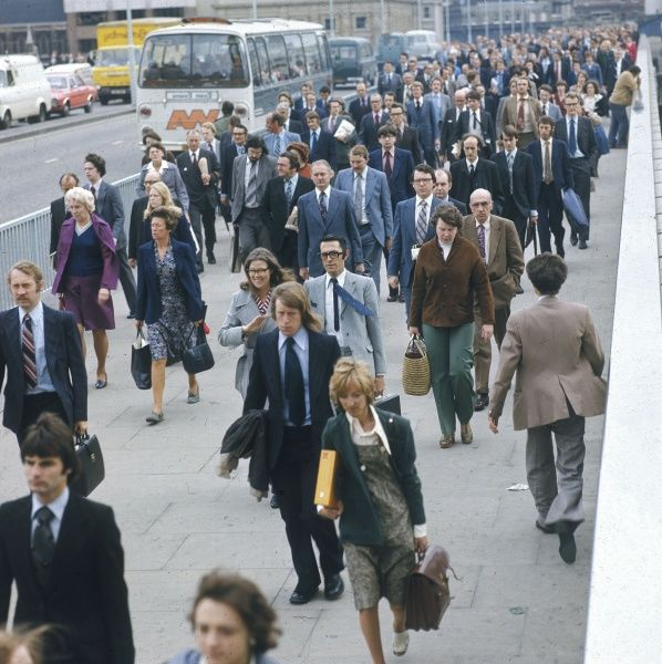 London commuters, most of them men in suits, walking over a bridge during the rush hour. Date: late 1970s