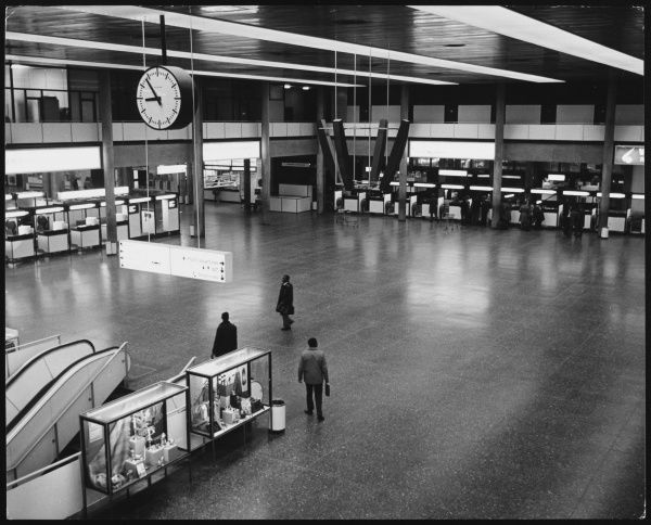 The vast interior of London Gatwick Airport, showing one the escalators beneath the clock