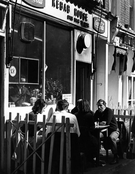 Dining outside a Kebab House on Charlotte Street, central London. Date: late 1960s