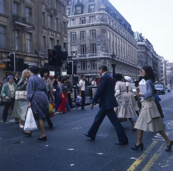 Pedestrians, office workers and commuters, using a pedestrian crossing on Oxford Circus, Oxford Street, central London. Date: 1978