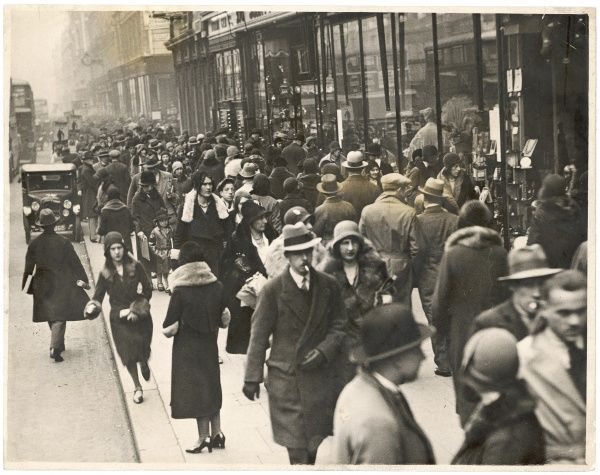 Crowds of smart shoppers, mostly wearing hats, going about their business in a central London street