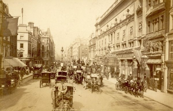 Horse-buses and cabs clatter along London's Piccadilly, while a carriage stops outside the 'Yorkshire Grey' public house