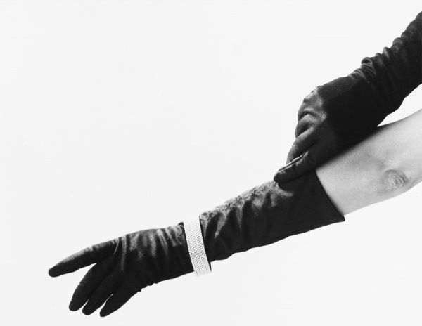 A pair of hands wearing long black gloves and jewellery