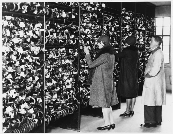 Two ladies in 1920s fashion of cloche hats and furs check through the New Scotland Yard Lost Property Office racks for their missing umbrellas. Metropolitan Police