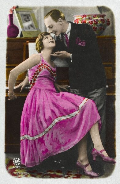 A woman in a fabulous pink dress happily accepts the admiring advances of a man as she sits at her piano
