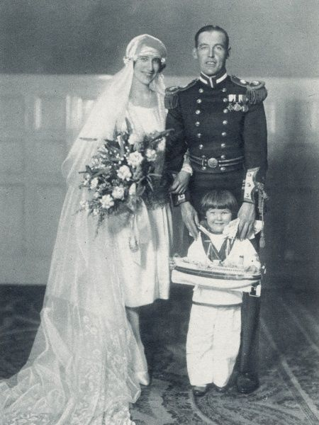 Lieutenant-Commander J.H. Edelsten, R.N. and his bride Miss Frances Masefield, with their pageboy, following their marriage at Holy Trinity Church, Sloane Street, London