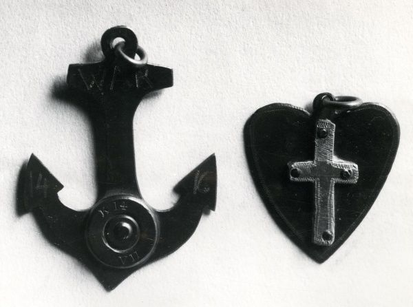 Two lucky charm mascot pendants worn by servicemen during the First World War. One is in the shape of an anchor, the other in the shape of a heart with a cross in the middle. Date: 1914-1918