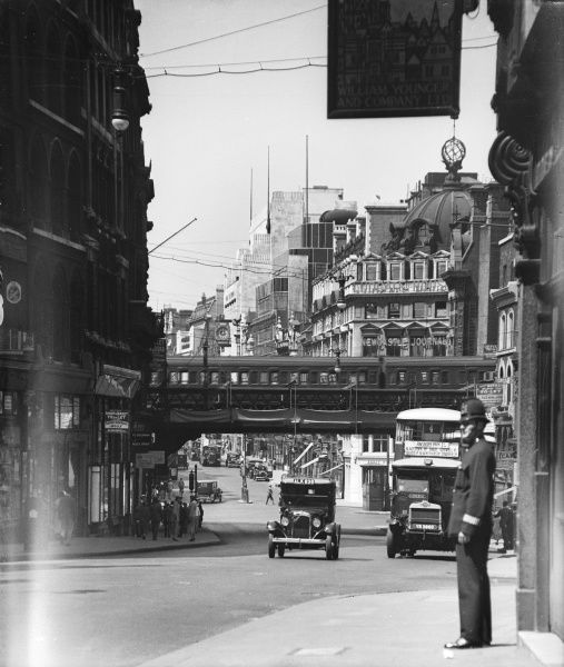 View looking down Ludgate Hill towards Ludgate Circus, showing a policeman on the right and a train going over the now dismantled railway bridge, London