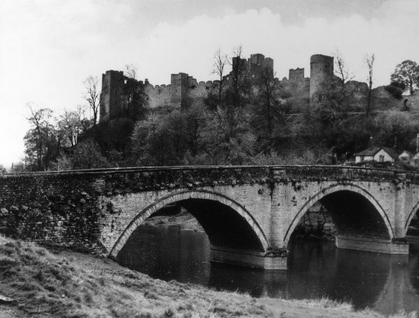 Part of the ruins of Ludlow Castle, Shropshire, England, with Dinham Bridge, spanning the River Teme, in the foreground. Date: 1930s