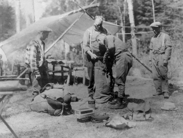 A group of lumberjacks setting up camp in a forest clearing. Date: early 1930s