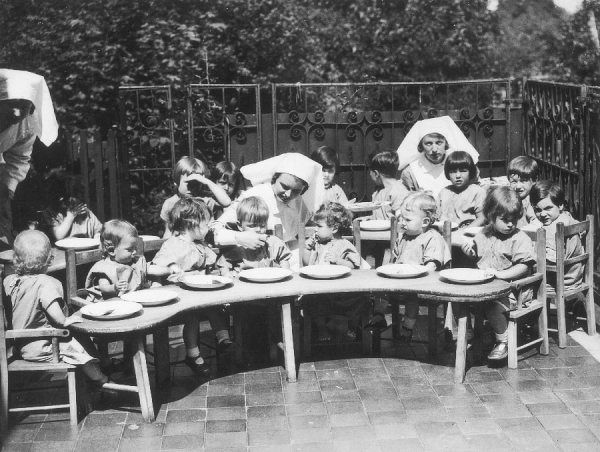 Small children being taught to eat correctly at a North London nursery school. During the fine weather, meals are taken outside