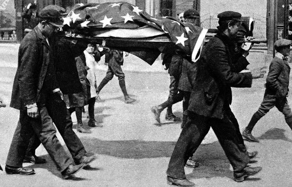 An American victim of the sinking of the 'Lusitania' being stretchered through Queenstown covered in the American flag. The 'Lusitania' was torpedoed by a German U-boat on May 7th 1915 with the loss of 1200 lives, including 100 Americans